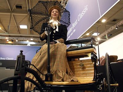 A Bertha Benz reenactor sitting on a replica of Motorwagen Nr. 1.